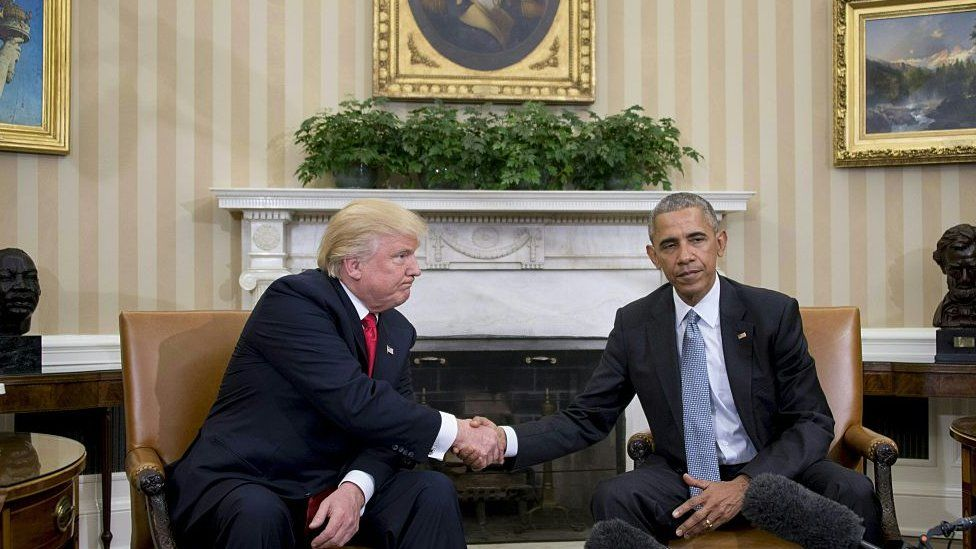 Donald Trump and Barack Obama shake hands in the Oval Office.