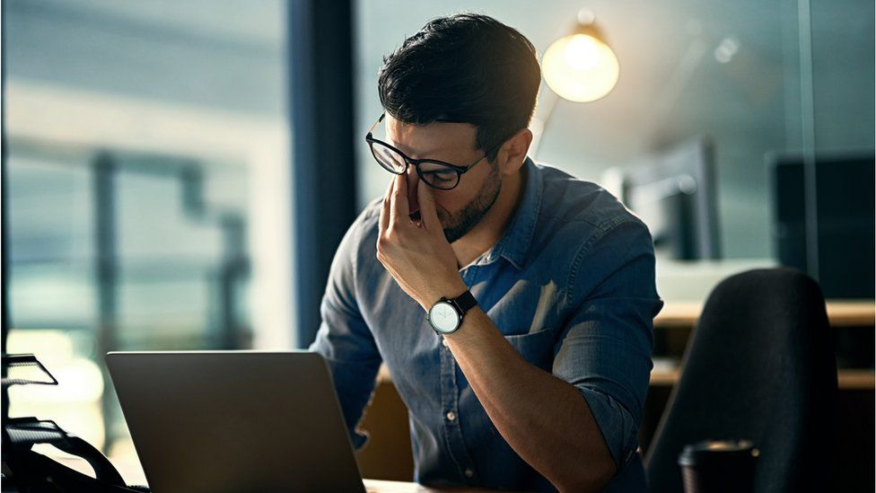 A stressed man pinches the bridge of his nose in frustration in front of his laptop in this photo illustration