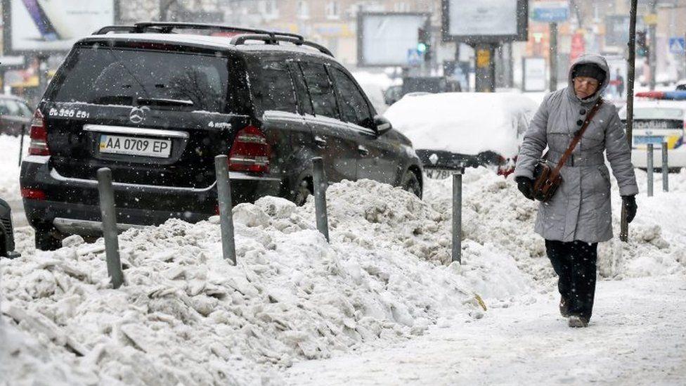 A woman walks past a snow dump along a road in Kiev, Ukraine. Photo: 9 January 2017