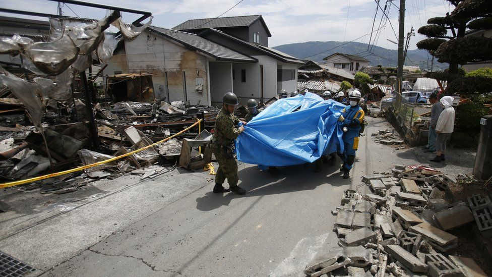 Rescue workers carry Yumiko Yamauchi, 93, on a stretcher covered in a blue plastic sheet, as they tread their way through broken tiles from a toppled house in Mashiki, Kumamoto prefecture, southern Japan (16 April 2016)