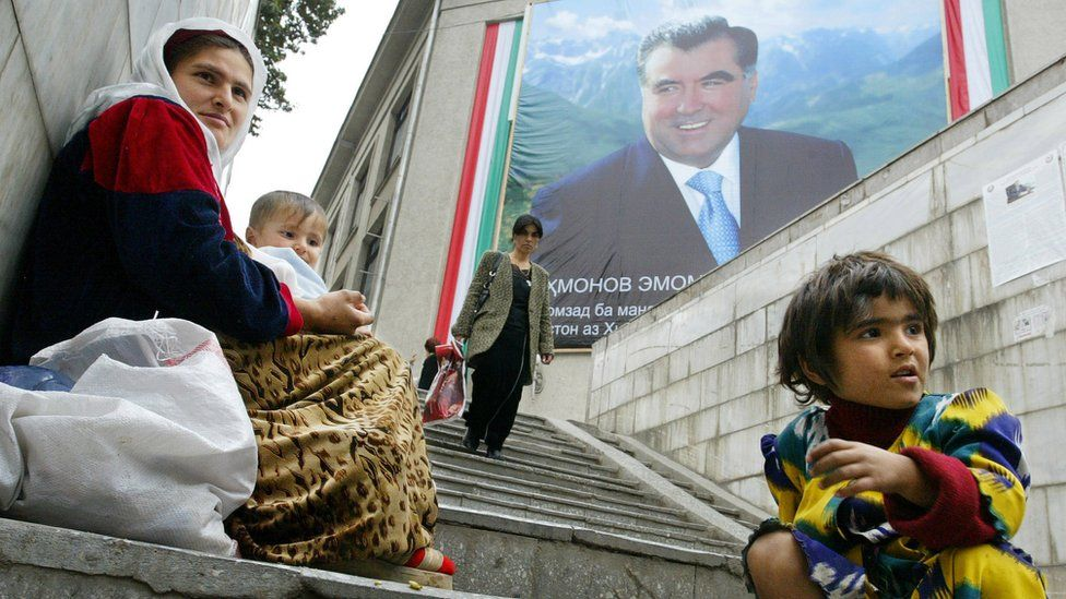 A mother and her children beg on a stairway, beneath a building with a huge poster of Tajik President Emomali Rahmon, 23 October 2006