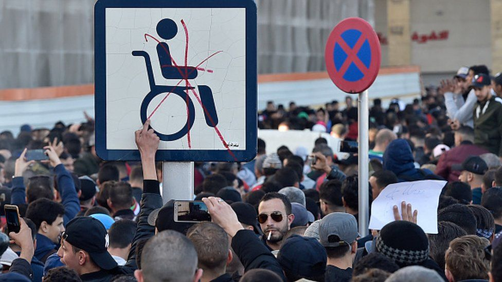 Algerian demonstrators hold a placard with the symbol of a man on a wheelchair