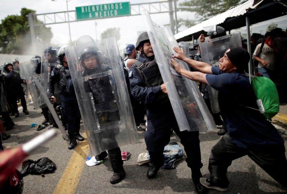 A Honduran man hits the shield of a riot policeman after storming the Guatemalan checkpoint to enter Mexico