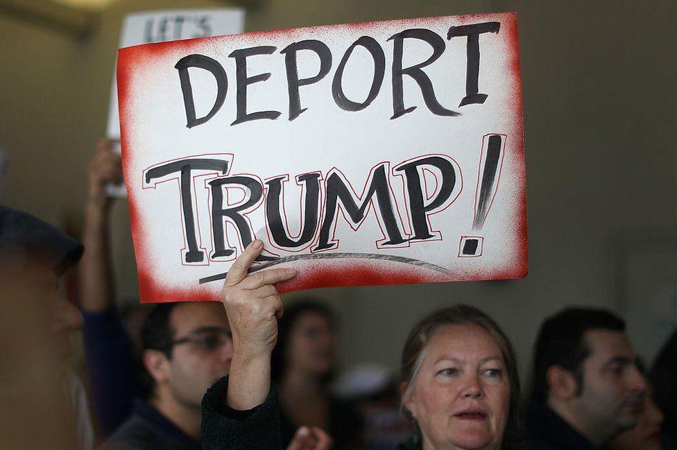 A Deport Trump sign