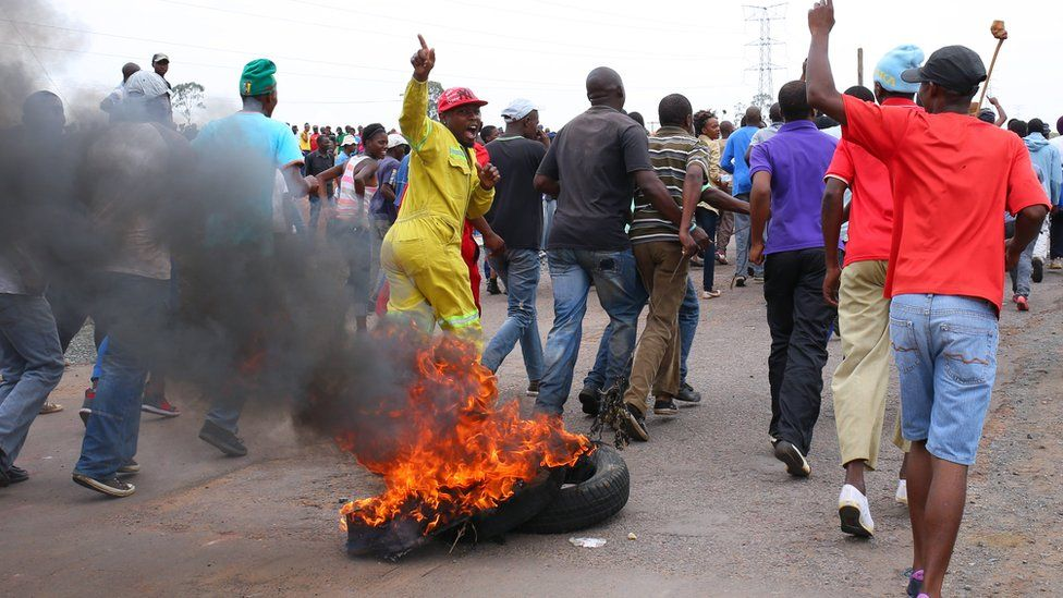 Protesting residents place burning tyres to create a roadblock as they march on the main road leading into the town of Bronkhorstspruit during a protest over poor public service delivery