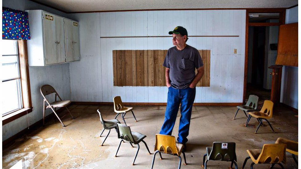 """Ronnie Carroll, 70, a mission worker from Roberstdale, Alabama, stands in a children's bible study room in the First Baptist Church in Baker. """"It's heartbreaking... I believe a tornado is better because you just lose everything at once, and it's gone, it takes it with it. A flood, they can see it. They can touch it, and they want to fix it but can't."""""""