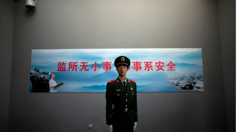 A paramilitary policeman stands guard underneath a surveillance camera at an entrance to the Number Two Detention Center in Beijing