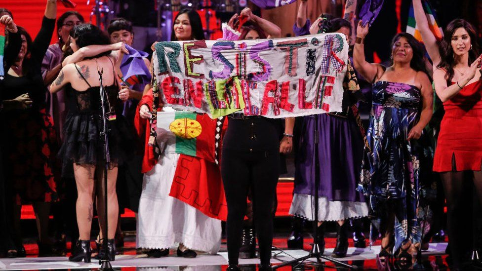 Singers with Chilean artist Mon Laferte show a banner reading 'Resist on the Street' at a concert last year