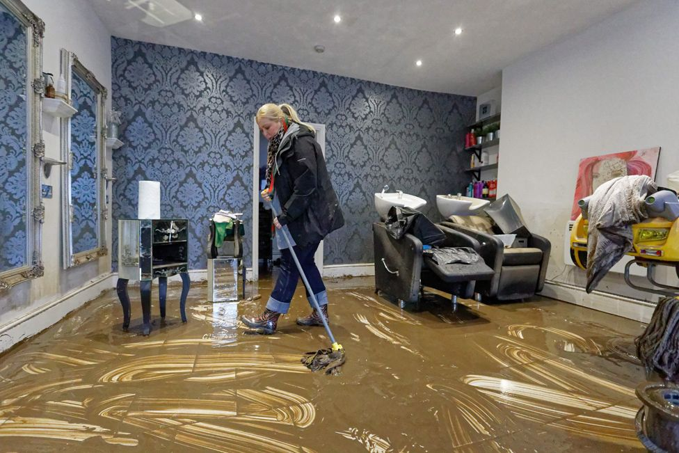 Laura Court mops up the floor of a hair dressers in Nantgarw, Wales.