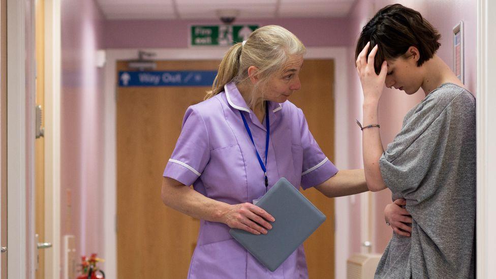 Nurse comforts a woman
