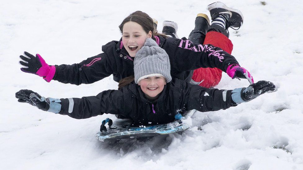 Two girls on a sled on a golf course near Penicuik, Midlothian