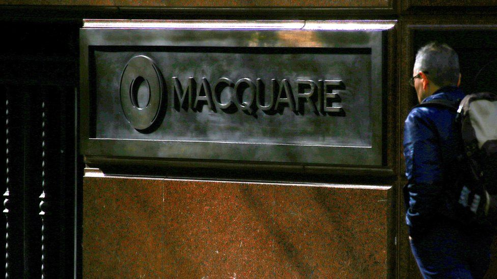 A pedestrian walks past the logo of Australia's biggest investment bank Macquarie Group Ltd on the outside of their Sydney office headquarters in central Sydney, Australia, July 18, 2017.