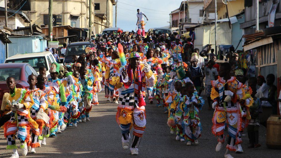 Lines of children parade in the street wearing multi-coloured feather outfits, led by an adult male. In the background, a man on stilts balances in the crowd in Sekondi Ghana
