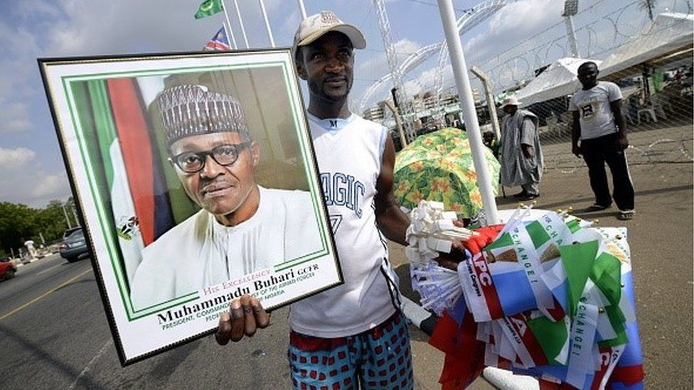 A vendor sells All Progressives Congress (APC) party flags and a framed photograph of President-elect Mohammadu Buhari ahead of tomorrow's handover ceremony in Abuja, on May 28, 2015
