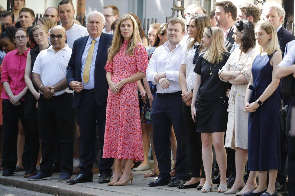 Carrie Symonds (C), girlfriend of Britain's new Prime Minister Boris Johnson, waits for the prime minister's arrival with members of staff in Downing Street in London on 24 July 2019