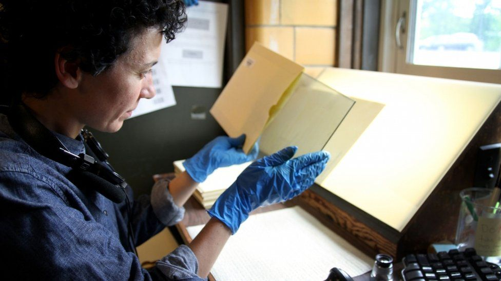 Curatorial assistant Anne Callahan inspects a plate before it is cleaned for scanning. She makes sure the metadata from the paper jacket is properly entered into the computer before the plate goes to be wiped down and then scanned.