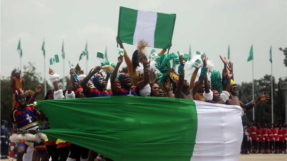 Members of an acrobatic band perform at Eagle Square in Abuja, Nigeria during the celebration for the country's 61st year of independence on Friday 1 October. There are a group of acrobats dressed elaborately with white face paint and wrapped in a large Nigerian flag jumping in a huddle. They look very happy and lively.