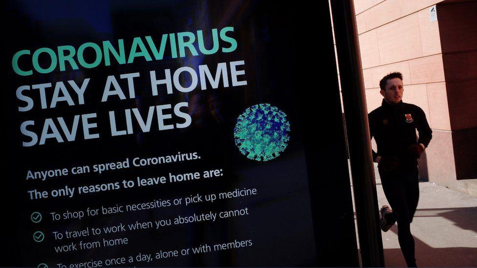 Man running past a coronavirus advice billboard