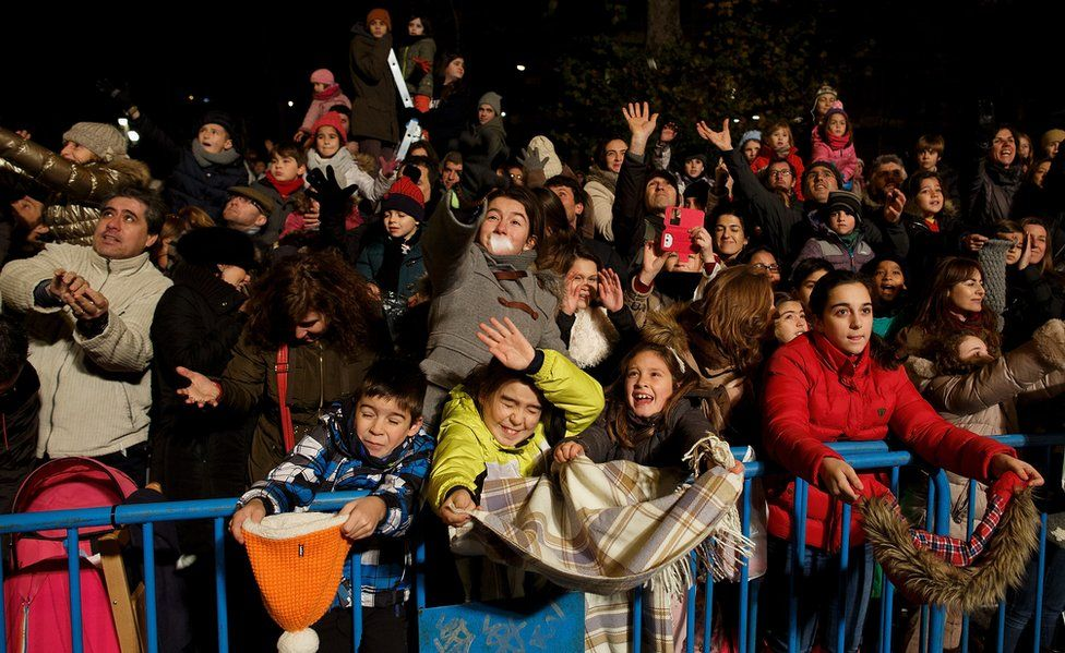 Children react as performers (not pictured) throw sweets to them during the 'Cabalgata de Reyes,' or Three Kings parade, on January 5, 2016