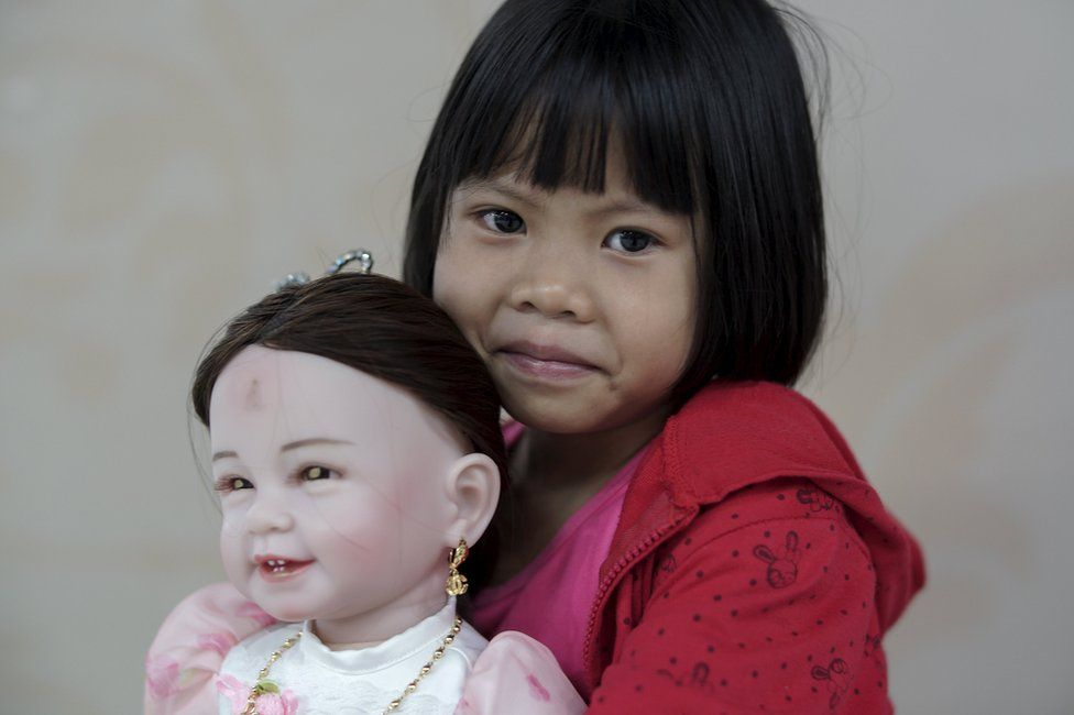"""Prew, 6, smiles as she holds up her """"child angel"""" doll inside a department store in Bangkok, Thailand, 26 January 2016"""