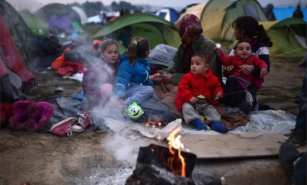 Refugees warm up by a fire at a makeshift camp along the Greek-Macedonian border near the village of Idomeni on February 28, 2016