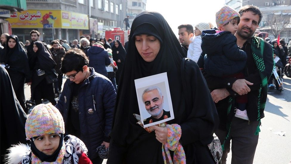 An Iranian woman holds a photo of picture of Iranian General Qasem Soleimani at his funeral in Tehran (6 January 2020)
