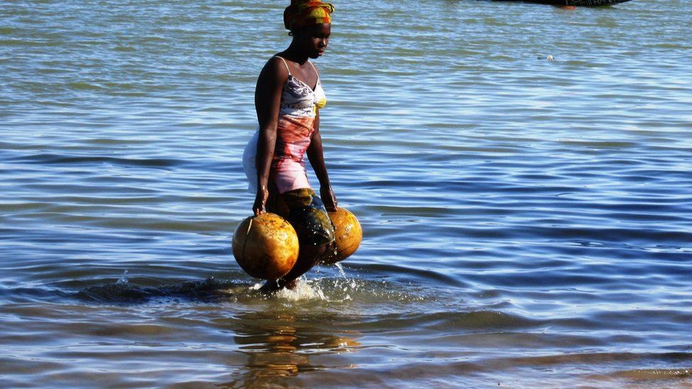 A Mali woman fetches water from a pond