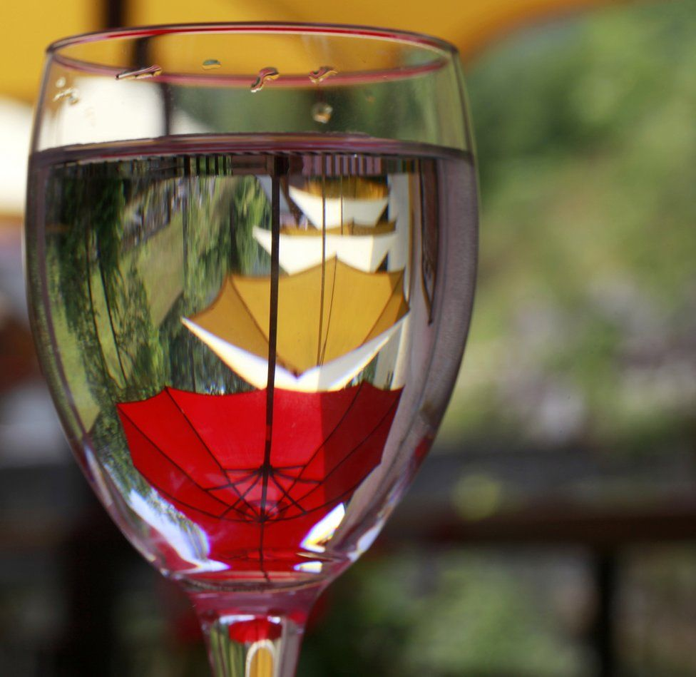 Umbrellas reflected in a wine glass