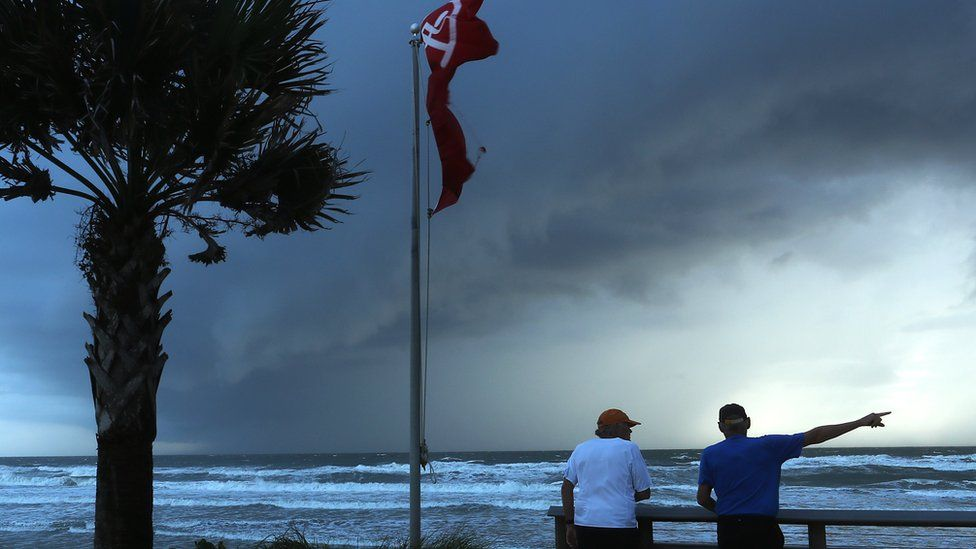 Two men stand looking out at the sea in Florida as the sky grows darker and more stormy