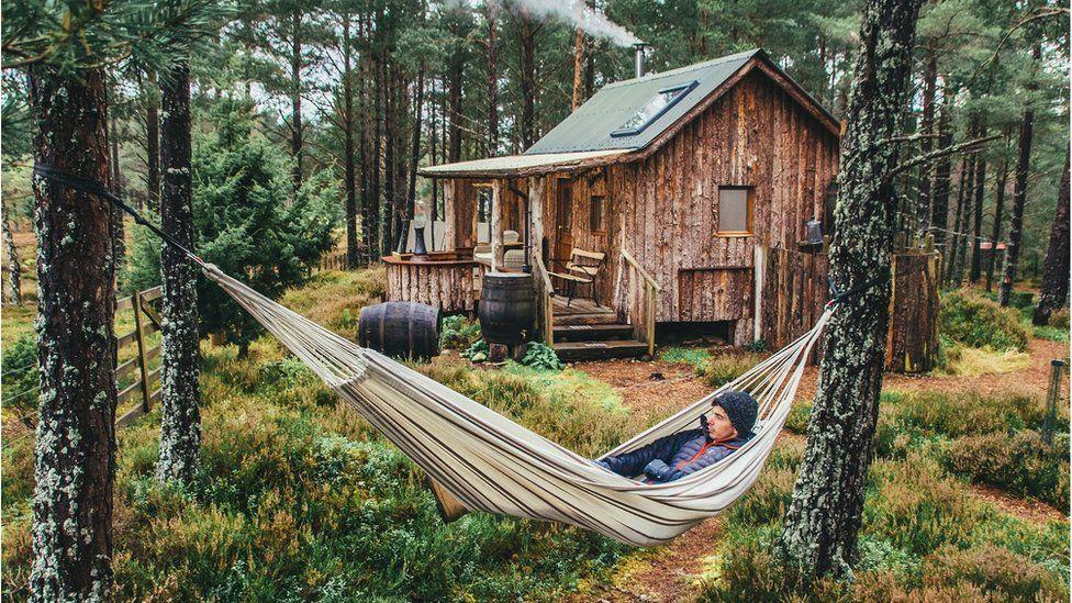 Man in hammock outside hut