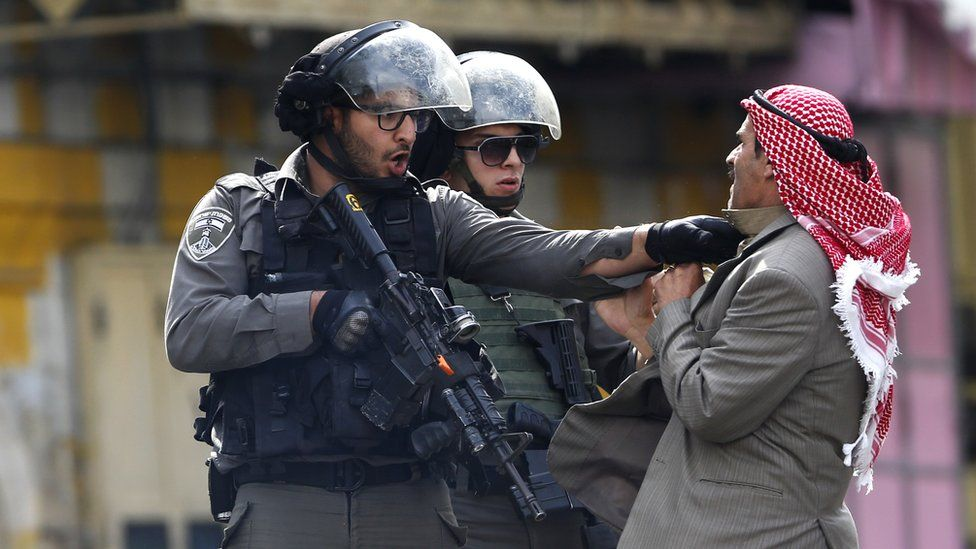 A Palestinian is pushed by an Israeli policemen amid clashes in Hebron, West Bank, Saturday, Oct. 10, 2015.