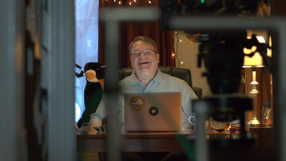 Picture of a man called John Lewis smiling at his laptop