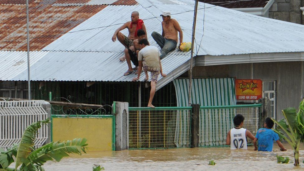 Residents sit on the roof of their submerged house due to floodwaters brought on by heavy rains caused by Typhoon Koppu in the town of Santa Rosa, Nueva Ecija province, north of Manila