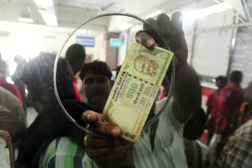 An Indian passenger uses a 500 rupee note to purchase rail tickets at Allahabad Railway station in Allahabad on November 9, 2016