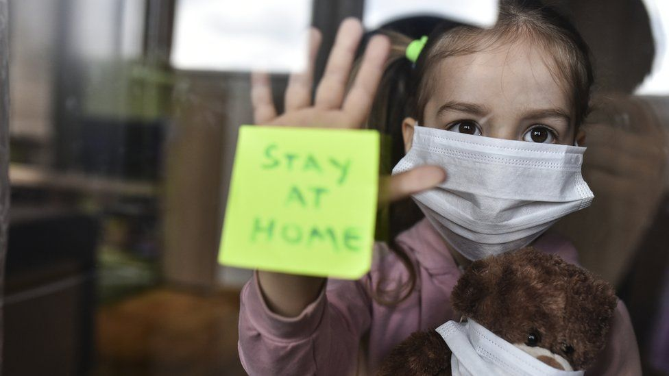"""Young girl with face covering holding a teddy bear with face covering holds her hand against a window, with a note stuck to the window reading """"Stay at home"""""""
