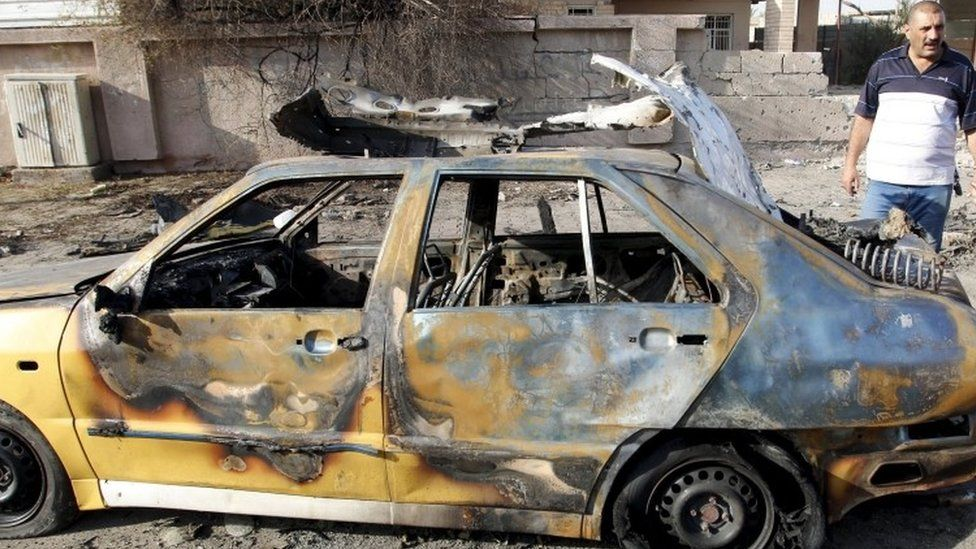 A destroyed vehicle is seen at the site of car bomb attack in Baghdad (13 July 2015)