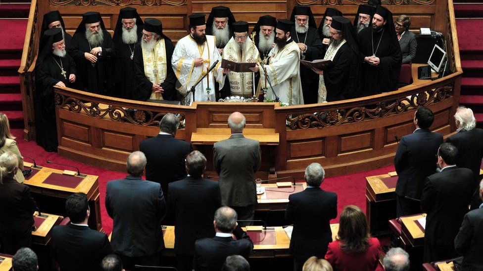 Orthodox priests conduct a blessing ceremony of the Greek parliament for the winter season in Athens on October 7, 2013