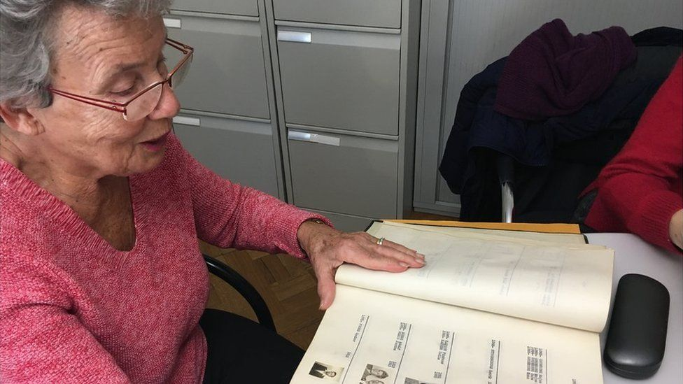 Agnes Hirschi looks at a book listing families protected by Carl Lutz's actions