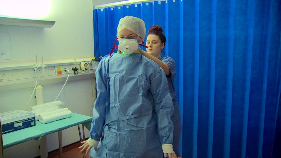 Medical staff put on their personal protective equipment.