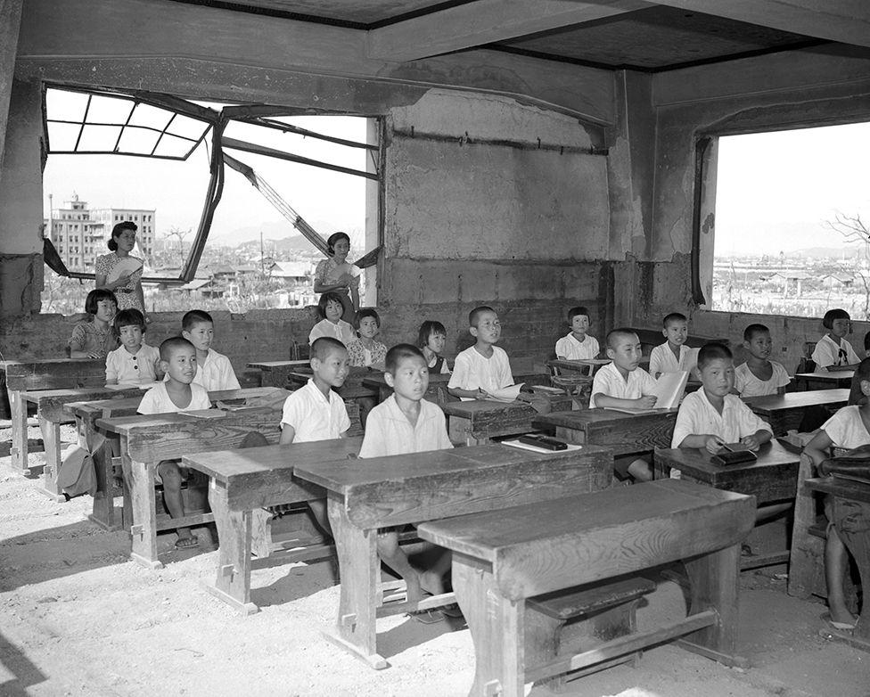1946年,學生在被毀壞的教室裏繼續上課,廢墟下仍然有數以千計的死難者。
