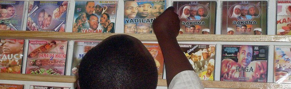 Man looking at Kannywood DVDs on a shelf