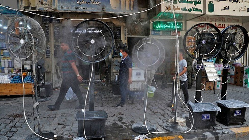 People walk past fans spraying air mixed with water vapour deployed by donors to cool down pedestrians