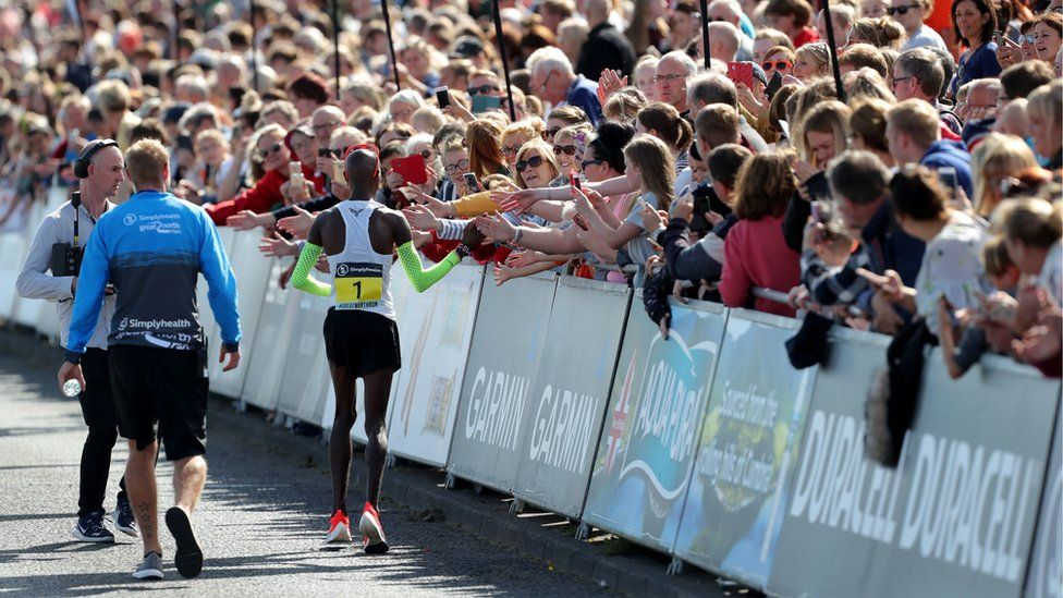 """Sir Mo Farah """"high fives"""" fans lining the side of the course"""