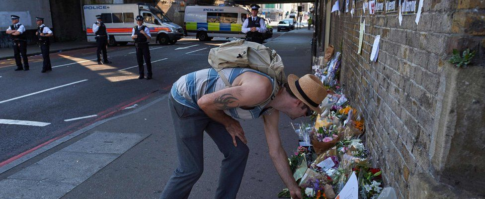 Man leaving flowers close to scene of attack