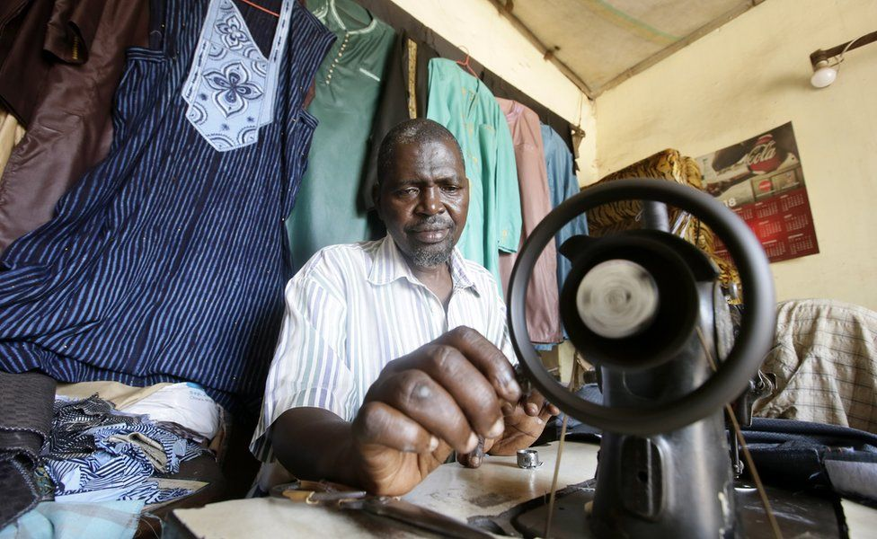 Tailor Mohamed Diallo sews at his local fashion shop in Dixinn neighbourhood, Conakry, Guinea, 17 February 2020.