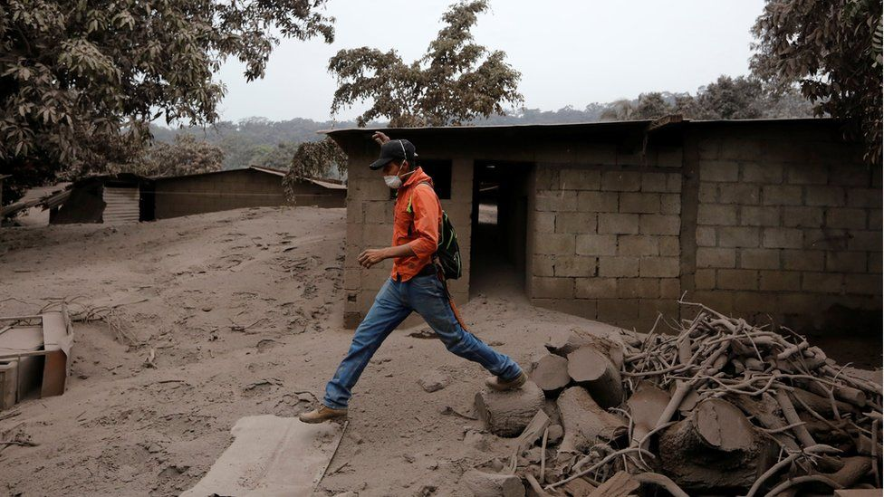 A man steps through debris in an area affected by eruption from Fuego volcano in the community of San Miguel Los Lotes in Escuintla, Guatemala June 4, 2018