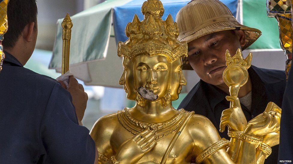 Shrine workers clean the statue of Brahma at the Erawan Shrine in Bangkok (19 Aug 2015)