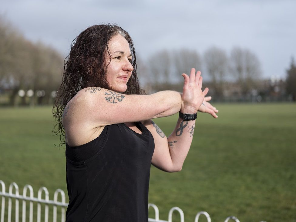 Photo of Michelle Bavin stretching her arms in running gear