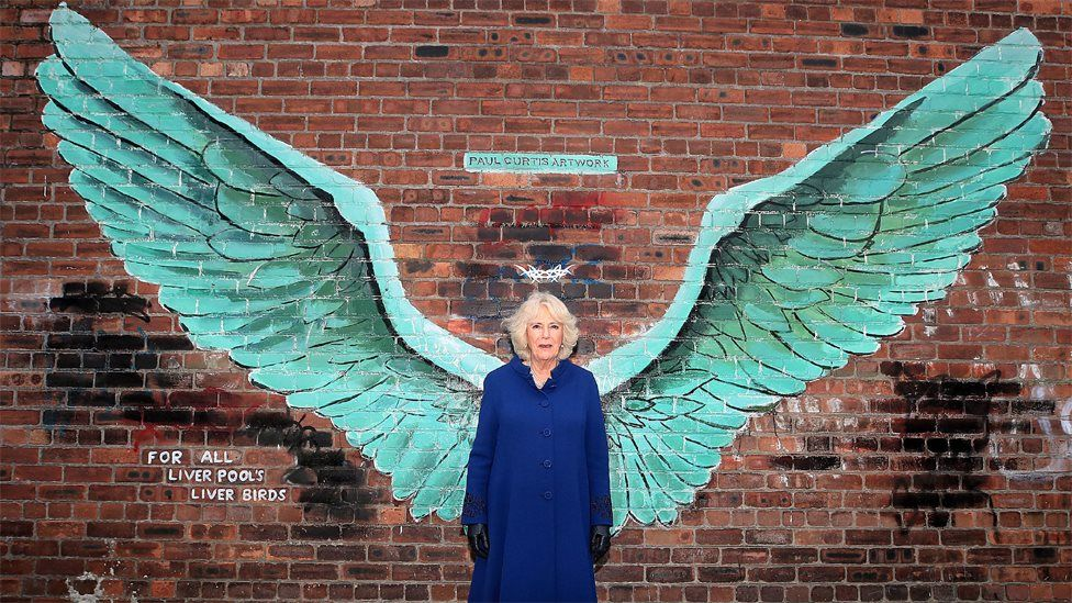 The Duchess of Cornwall stands between the wings of artist Paul Curtis' mural entitled For All Liverpool's Liver Birds