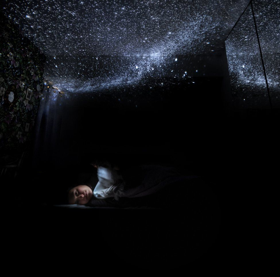 An image of a child in a bedroom with a constellation of lights above representing stars